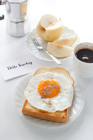 fried egg on toast, fruit, black coffee and text Hello Sunday Stock Photo