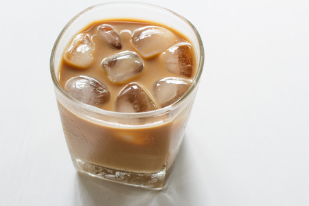 Glass of cold iced coffee on white table.