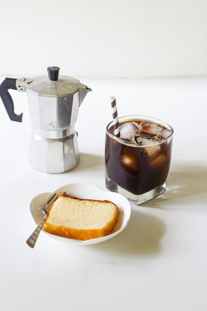 glass of cold iced coffee with homemade butter cake on white table. Stock Photo