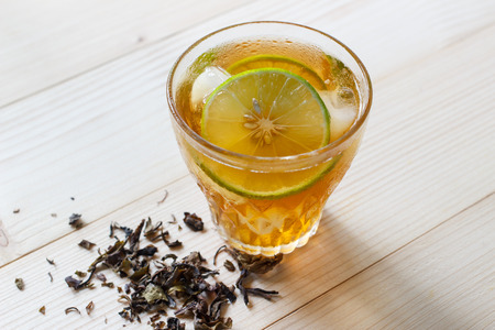 Glass of iced tea with lime slices on a wooden table background