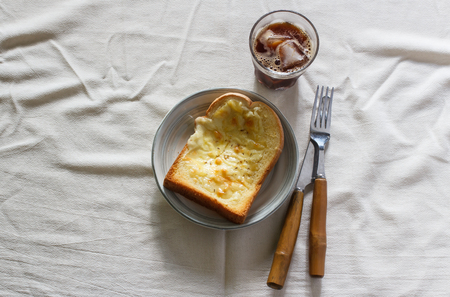 Toasted bread with garlic and cheese, glass of cold iced coffee in cloth background. Banco de Imagens