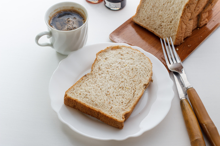 slice hole wheat bread with black coffee on white table.
