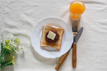toast bread with red bean paste, butter and fresh orange juice. Stock Photo