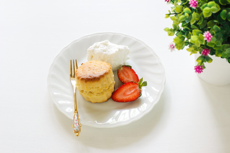 Traditional British Scones with clotted cream, fresh strawberry.