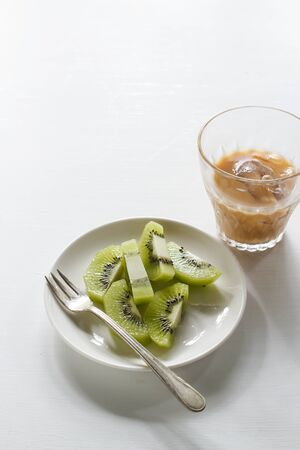 kiwi fruit served on small plate with cole iced coffee.