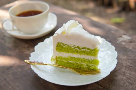 pandan chiffon cake with coconut sauce serve with glass of tea put on old table. Stock Photo