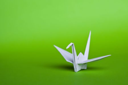 A white origami crane on a green background