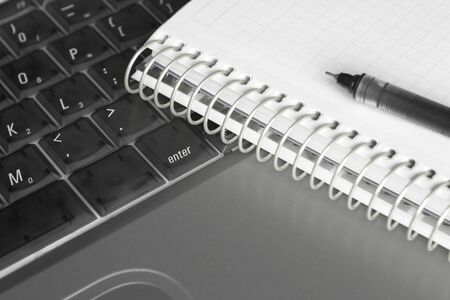 Close-up of a notebook and a pen on a semi-transperant laptop keyboard. Focus around the Stock Photo - 3204702