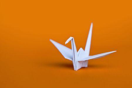 A white origami crane on an orange background