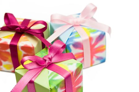 Three origami gift boxes on a white background. Focus on the pink ribbon of the box in front.