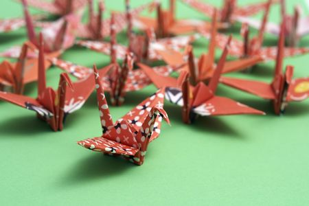 A group of origami birds on a green background