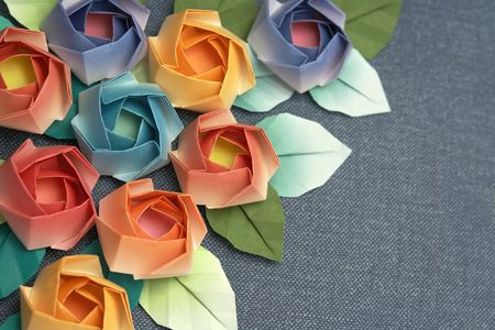 Origami roses decoration on a greyish blue background Stock Photo