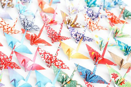 A group of origami cranes facing the same direction on a white background