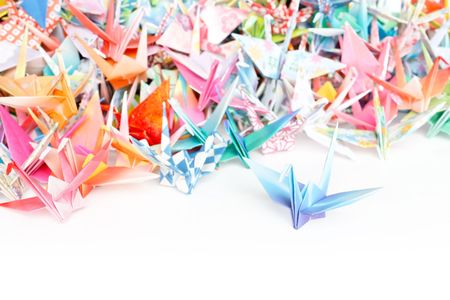 Photo of a pile of origami cranes on a white background. Shallow depth of field.  Stock Photo