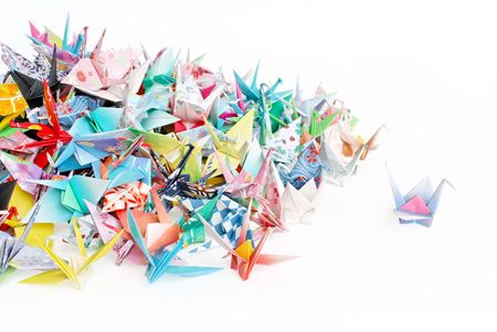 A paper crane standing out from a pile of paper cranes