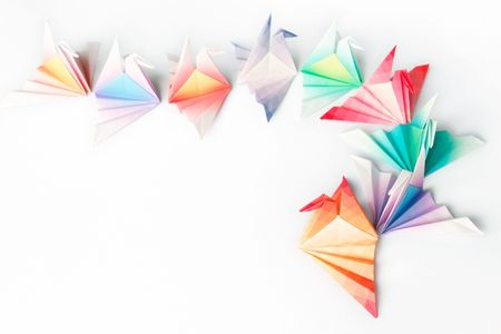A queue of colourful origami birds on a white background. High key soft focus. Stock Photo - 6240088