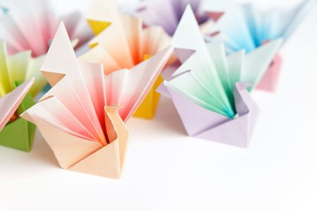 A group of colourful origami birds facing the same direction, on a white background. High key and shallow depth of field.