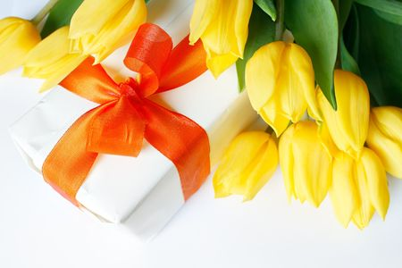 A white chocolate box surrounded by yellow tulips