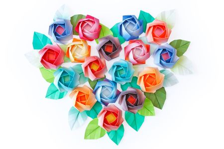 Paper roses arranged in a heart shaped on a white background