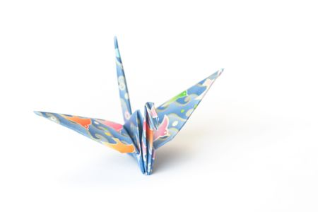 An origami bird with birds-pattern on a white background. Shallow depth of field, focus on the head.