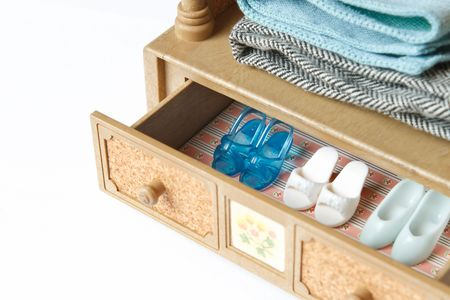 A collection of doll shoes in a drawer. Focus on the blue shoes.