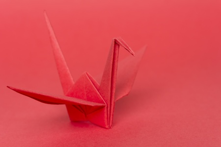 A red paper bird on a red background, shallow depth of field  Stock Photo