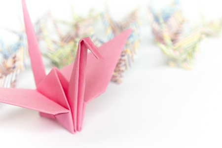 A big pink paper bird and a group of small paper birds, shallow depth of field