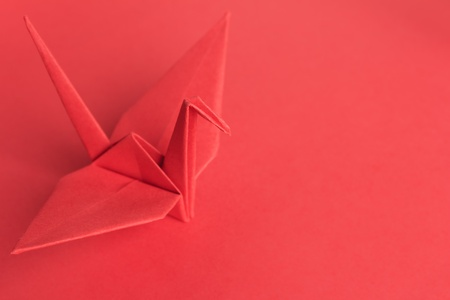 A red paper bird on a red background. Shallow depth of field