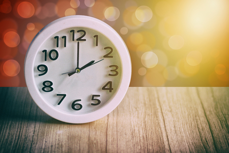 white circle clock at 2pm on wooden table with bokeh background