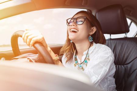 행복한 기분으로 차를 운전하는 아시아 여자.