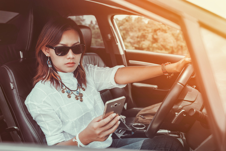motorcar: Asian woman looking at a smartphone in the car. Stock Photo