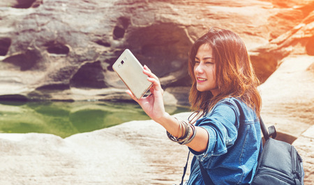 intend: Asia woman taking a photo at Sampanbok natural stone park the grand-canyon of Ubonratchathani Thailand Stock Photo