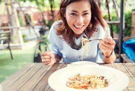 Asiatinnen, die köstlich, Fokus auf Gesicht essen Standard-Bild