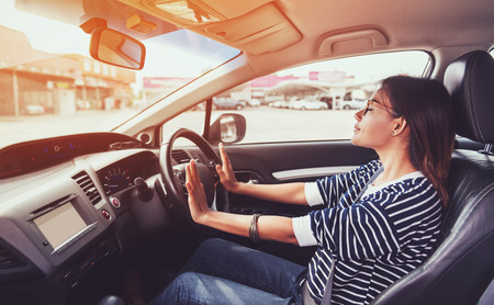 Asian woman driving a car in a happy mood,focus on hand Stock Photo