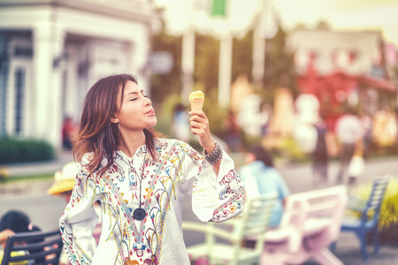 Photos of Asian women eating ice cream and  stand in hot weather. The emotional happiness,Focus on face