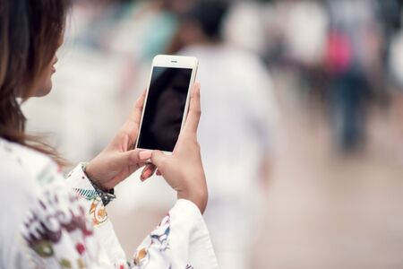 Photos of Asian women using cell phones in the outdoors,Focus on Focus on hands