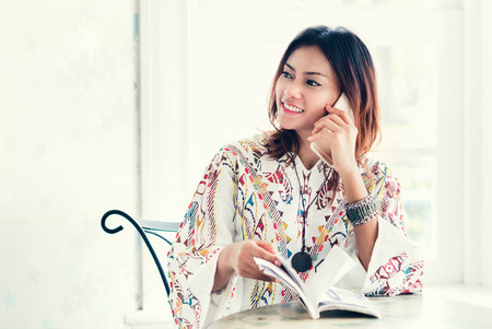 Asian women have a sense of comfort when phoning in the shade,Focus on face