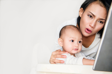 Pictures of Asian women embrace the boy and look at the taplet screen with intent.Focus on face Stock Photo