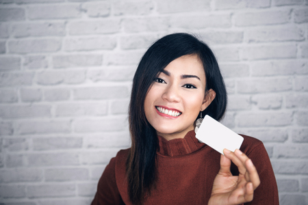 Asian girl raise white cards and good .Focus on face