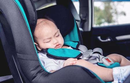 El niño asiático está durmiendo en su asiento de coche. Se centran en la cara Foto de archivo