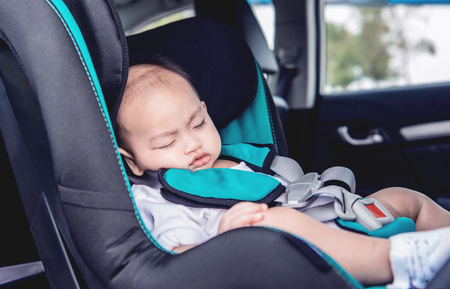 The toddler Asian boy is sleeping at his car seat.Focus on face Stockfoto