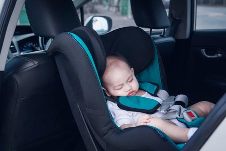 De Aziatische peuterjongen slaapt in zijn autostoeltje. Focus op gezicht