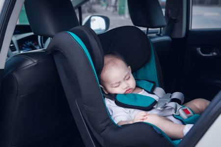 Der asiatische Junge schläft auf seinem Autositz. Konzentrieren Sie sich auf das Gesicht