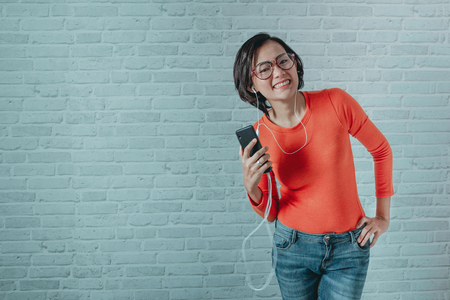 Asian women are listening to music with his mobile phone In a happy mood.Focus on the face