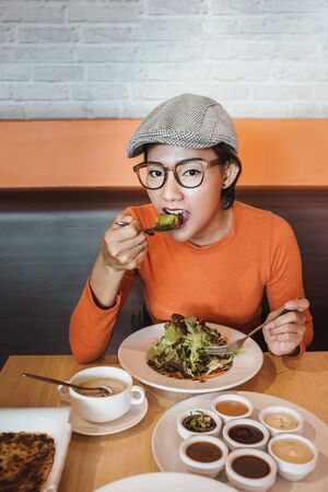 Pictures of Asian women have fun when eating salad on her plate.Focus on face