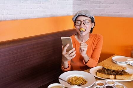 Asian woman is smiling when looking at her cell phone and eating in a restaurant. Happy mood.Focus on face Фото со стока