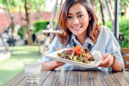 Asian women sit and hold a shrimp salad dish on the outdoor table. Happy smile.Focus on shrimp salad dish  Banco de Imagens