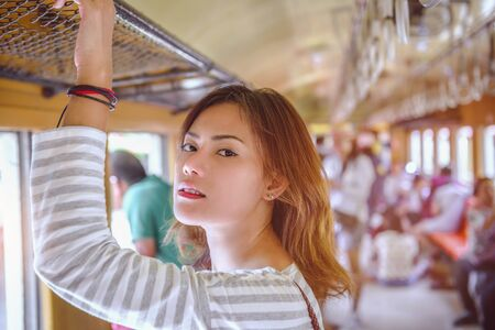 Picture of an Asian woman traveling back to his home by an old train.Focus on face