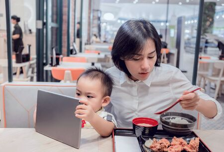 Asian mother is eating at a restaurant. While his son sat watching the tablet with interest.Focus on baby face