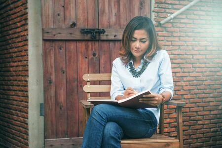 Asian woman writing her notebook at an outdoor restaurant.Focus on face Reklamní fotografie - 133126268